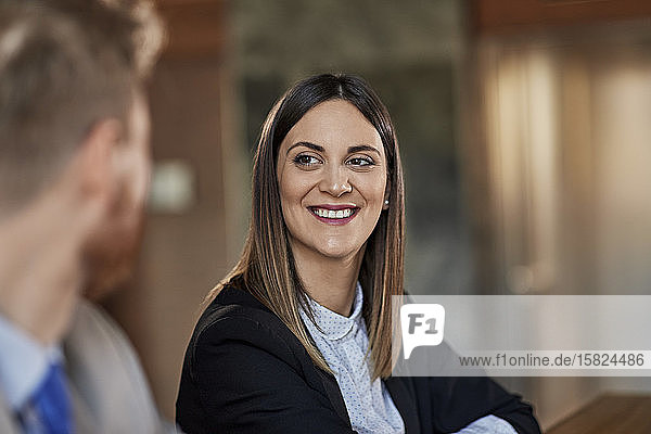 Portrait of a smiling businesswoman looking at colleague