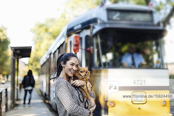 Glückliche junge Frau mit Hund an der Straßenbahnhaltestelle in der Stadt Glückliche junge Frau mit Hund an der Straßenbahnhaltestelle in der Stadt