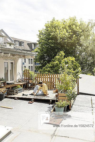 Junger Mann baut Terrasse auf dem Dach