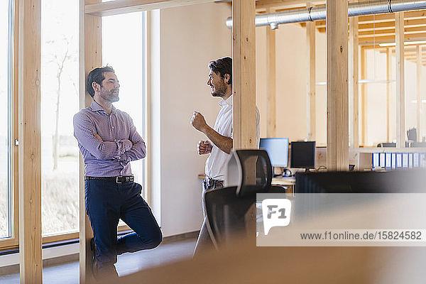 Zwei Geschäftsleute unterhalten sich im hölzernen Großraumbüro