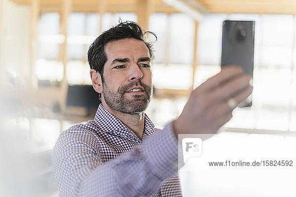 Geschäftsmann beim Selfie im hölzernen Großraumbüro