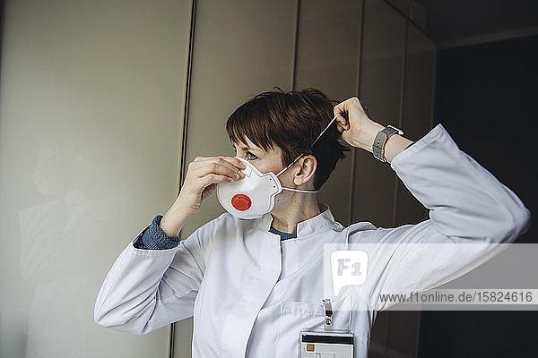 Female doctor putting on FFP3 mask