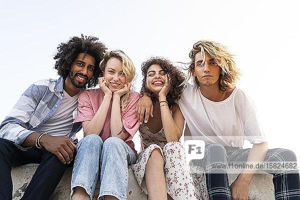 Porträt von glücklichen Freunden  die im Freien an einer Wand sitzen