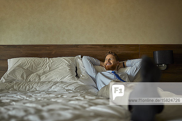 Businessman lying on bed in hotel room