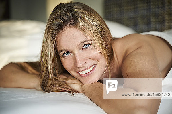 Portrait of happy blond young woman lying in bed