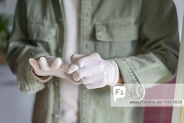Mann zieht Schutzhandschuhe an
