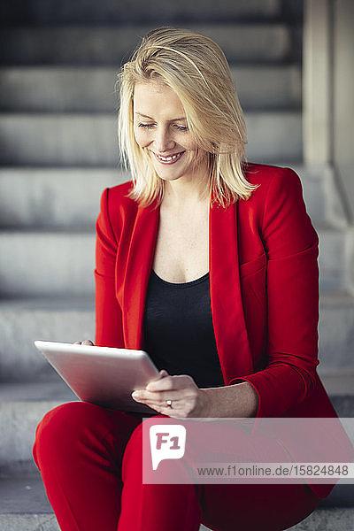 Blonde Geschäftsfrau in rotem Anzug und mit digitalem Tablet in einem Bürogebäude