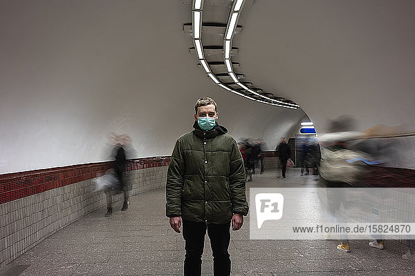 Young man with face mask standing isolated in subway underpass  with people moving around him