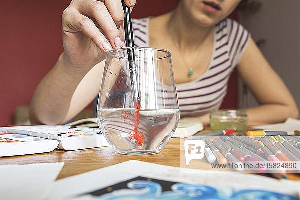 Frau malt mit Aquarellfarben