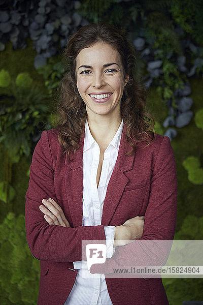 Portait of happy businesswoman in green office