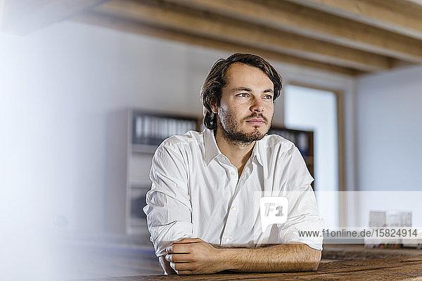 Porträt eines Geschäftsmannes im hölzernen Großraumbüro