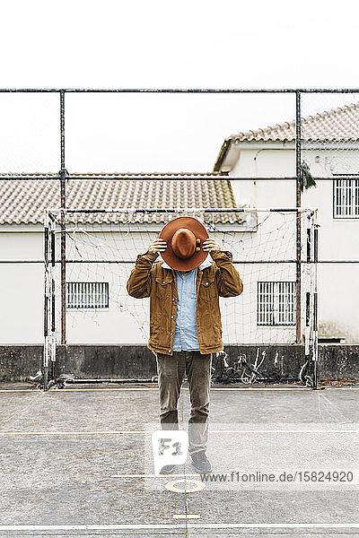 Mann steht auf Sportplatz und bedeckt sein Gesicht mit einem Hut