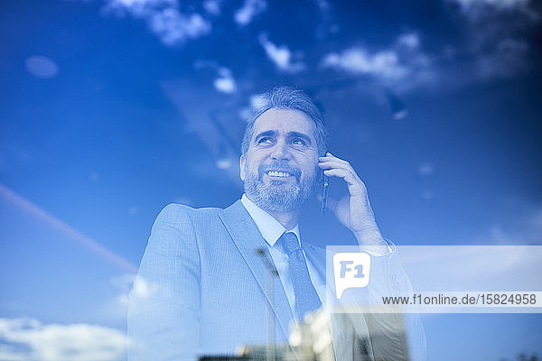 Portrait of a mature businessman on the phone behind windowpane