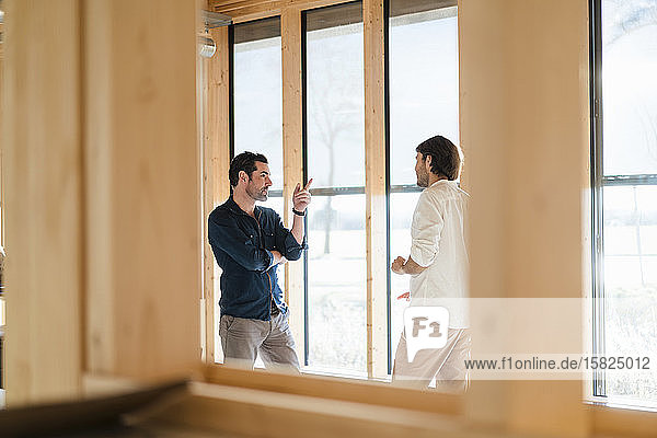 Zwei Geschäftsleute unterhalten sich am Fenster in einem hölzernen Großraumbüro