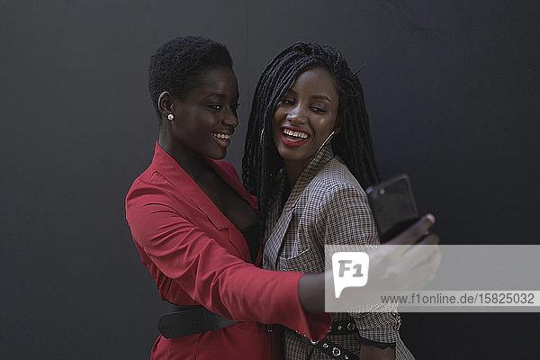 Zwei Frauen beim Selfie vor grauer Wand