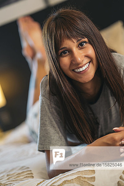 Porträt einer lächelnden jungen Frau  die zu Hause auf dem Bett liegt