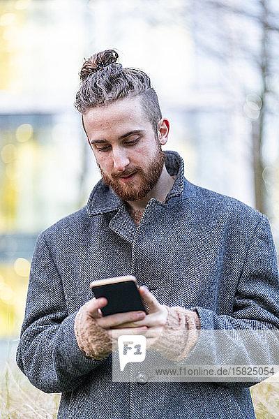 Junger Mann benutzt Handy in der Stadt Junger Mann benutzt Handy in der Stadt