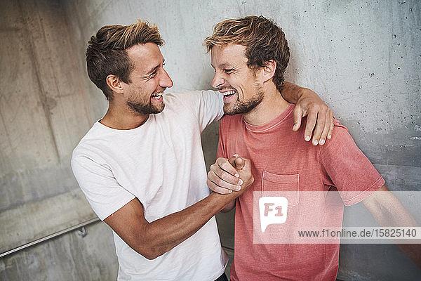 Zwei glückliche Freunde umarmen sich und schütteln sich die Hände