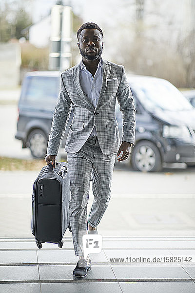 Businessman with suitcase walking on pavement