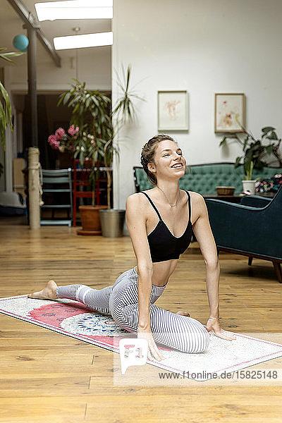 Junge Frau  die in ihrem Wohnzimmer Yoga praktiziert