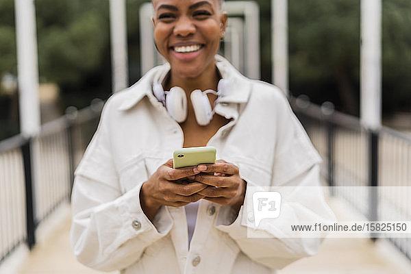 Porträt einer glücklichen Frau mit Handy in der Hand auf einer Brücke