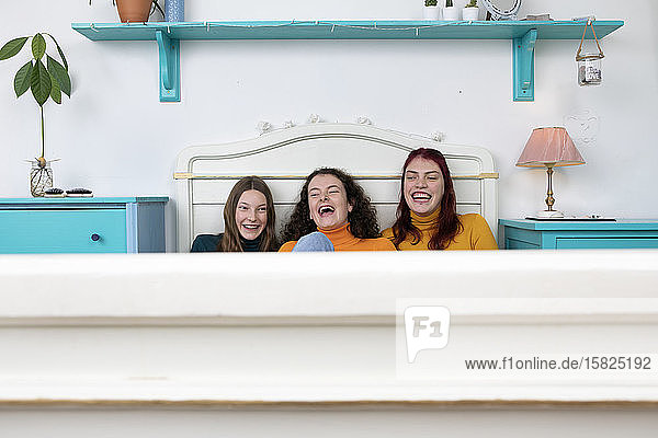 Portrait of three laughing sisters sitting side by side on bed