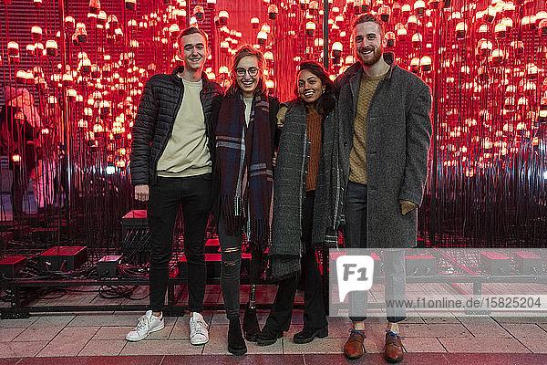Porträt glücklicher Freunde vor roten Glühbirnen Porträt glücklicher Freunde vor roten Glühbirnen