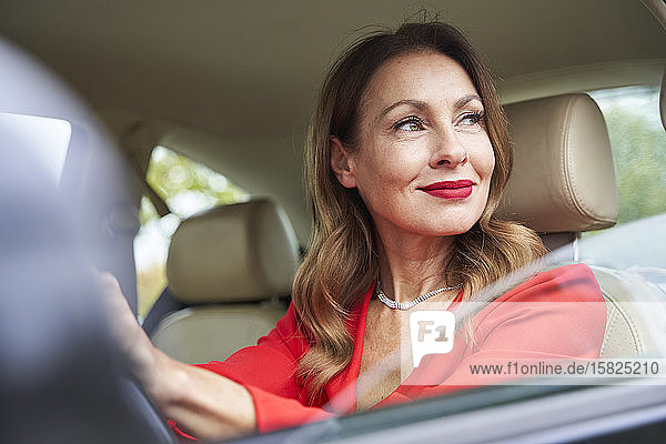 Portrait of smiling mature woman looking out of car window
