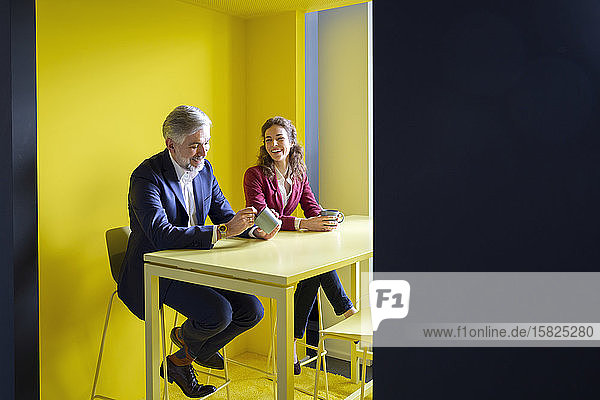 Businessman and businesswoman having a coffee break in office cubicle