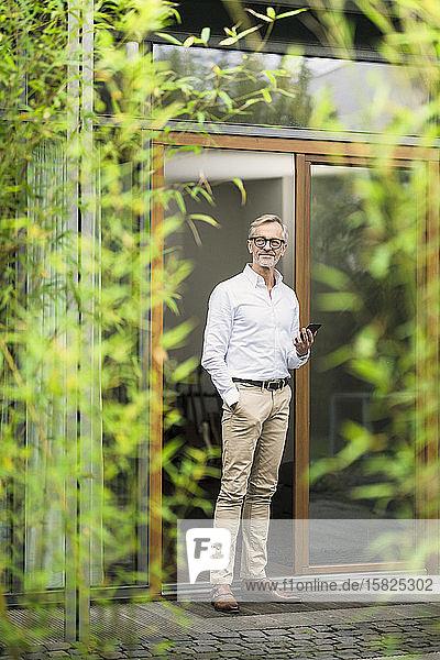Älterer Mann mit grauen Haaren hält Smartphone vor seinem modernen Design-Haus im Bambusgarten
