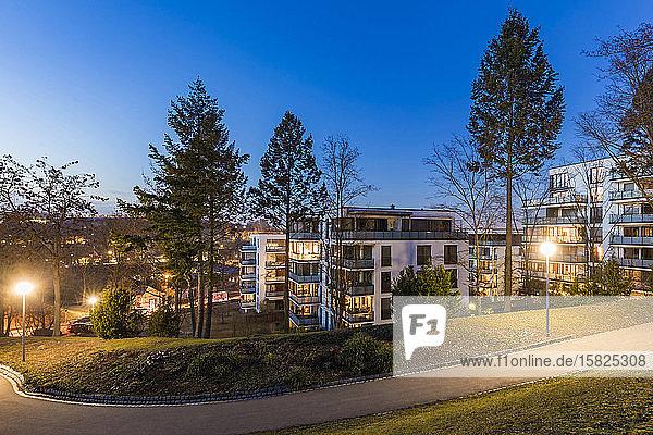Deutschland  Baden-Württemberg  Stuttgart  Leerer Fußweg im öffentlichen Park in der Dämmerung mit modernen Wohnungen im Hintergrund