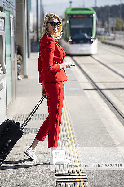 Blond businesswoman wearing red suit  waiting for the next train