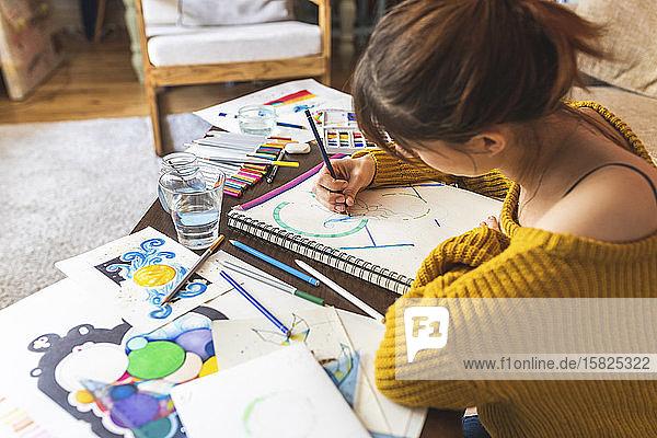 Schrägansicht einer Frau  die zu Hause mit Farbstift zeichnet