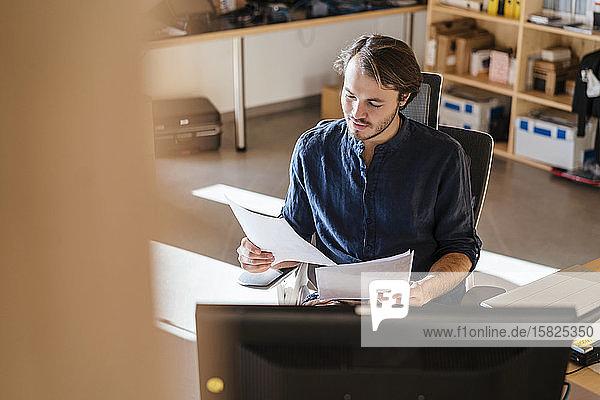 Geschäftsmann liest Dokument am Schreibtisch im hölzernen Großraumbüro