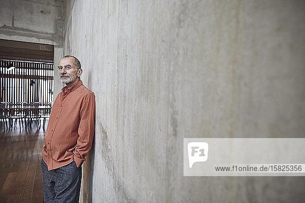 Kreativer Geschäftsmann lehnt in seinem minimalistischen Büro an der Wand