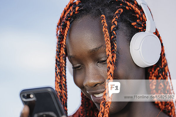 Porträt einer lächelnden Teenagerin mit Kopfhörer und Smartphone im Freien