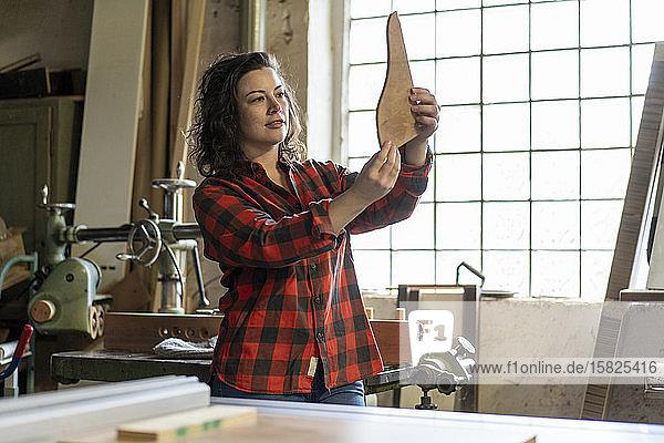 Schreinerin hält Werkstück in ihrer Werkstatt