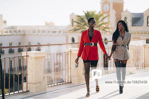 Zwei Frauen  die Händchen halten und in der Stadt spazieren gehen