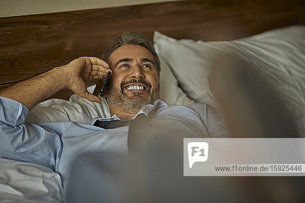 Laughing businessman lying on the bed in hotel room talking on the phone
