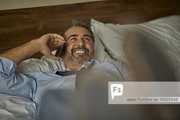 Lachender Geschäftsmann liegt auf dem Bett im Hotelzimmer und telefoniert
