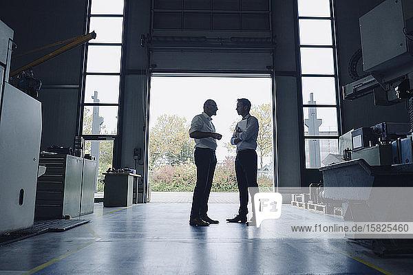 Zwei Männer unterhalten sich am offenen Tor in einer Fabrik