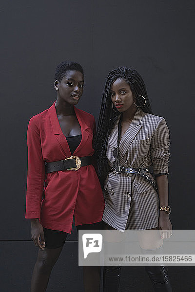 Zwei Frauen vor grauer Wand