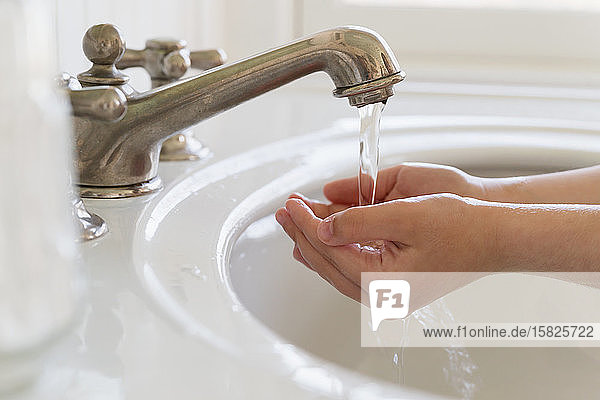 Close-up of girl (6-7) washing hands