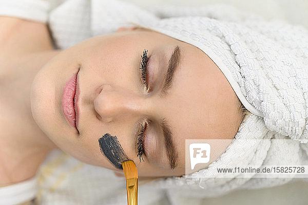 Auftragen einer Gesichtsmaske auf das Gesicht einer Frau im Spa