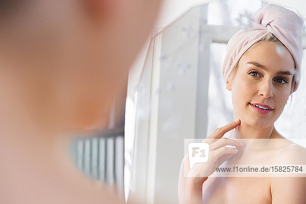 Woman wearing towel wrapped around her head looking into mirror