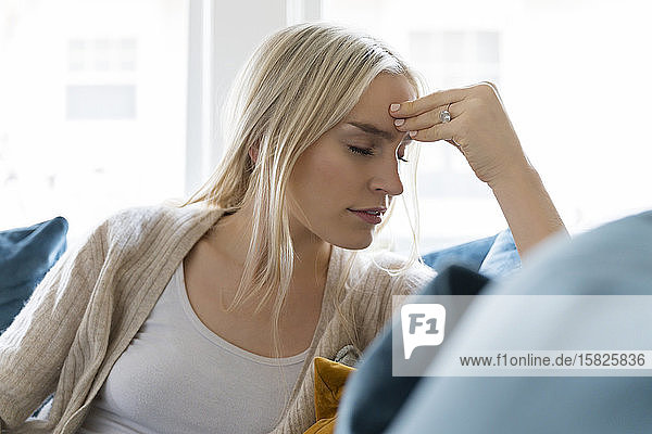 Woman with headache siting on sofa