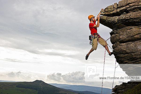 Felskletterer auf einer Klippe im Peak District in England
