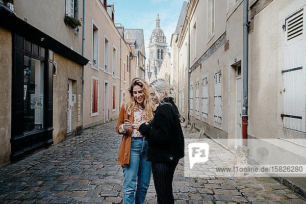 Junge Frauen  die in einer französischen Stadt mit ihrem Smartphone nach dem Weg suchen