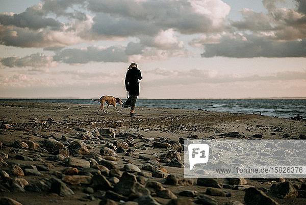 Frau  die bei Sonnenuntergang mit dem Hund am Strand spazieren geht