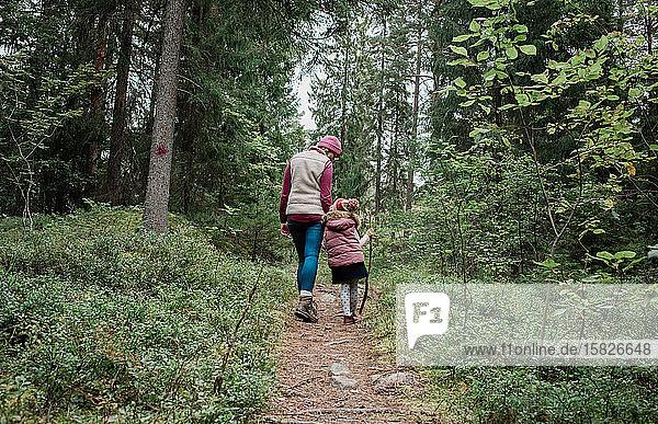 Mutter hält ihre Töchter an der Hand  als sie im Herbst durch den Wald geht
